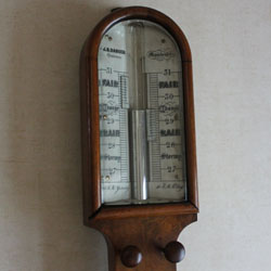 The head of an antique stick barometer showing the mercury level when in use