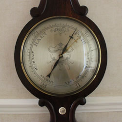 A 10in wheel barometer with long blued steel indicator hand, and a short brass set hand controlled by ivory knob below the silvered dial